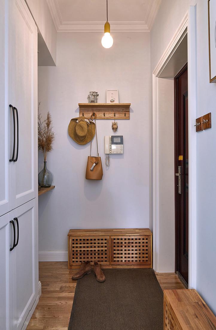 北欧风格的玄关设计比较清爽,白色的墙面木色的挂钩以及换鞋收纳...